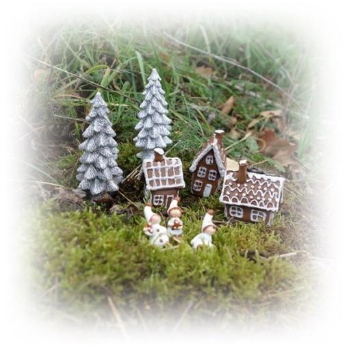 Tre små hus i skogen med lekande barn